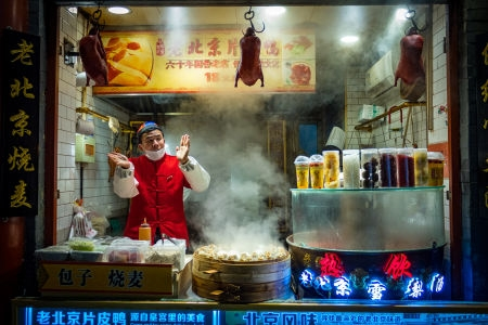 Vendor at Wangfujing street food market offers Beijing duck